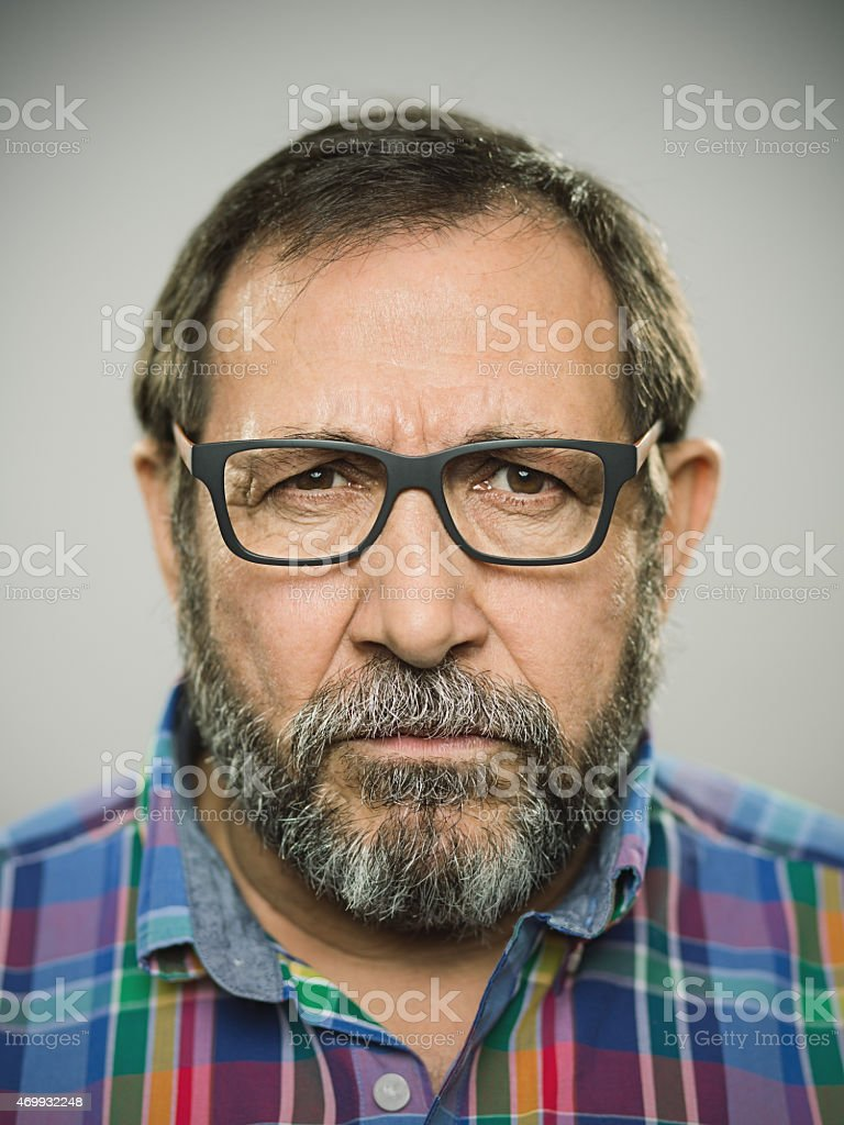 Portrait of an angry spanish man with glasses and beard. stock photo