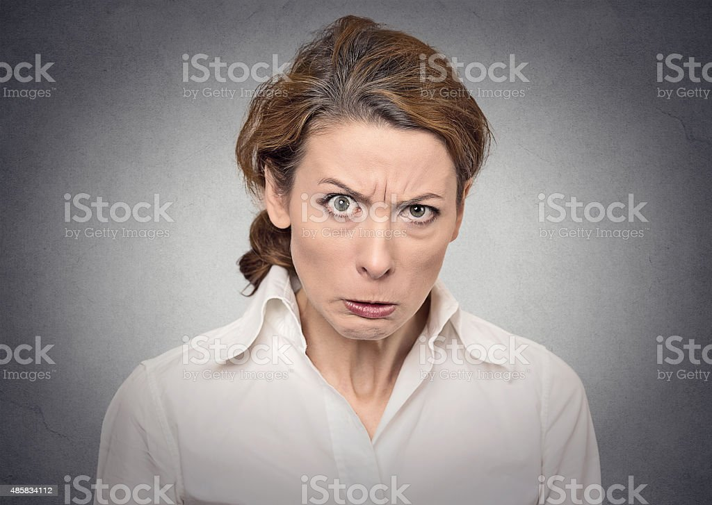 portrait of an angry grumpy funny looking woman isolated on gray wall...