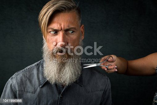 Portrait of an anxious bearded man in the barber shop