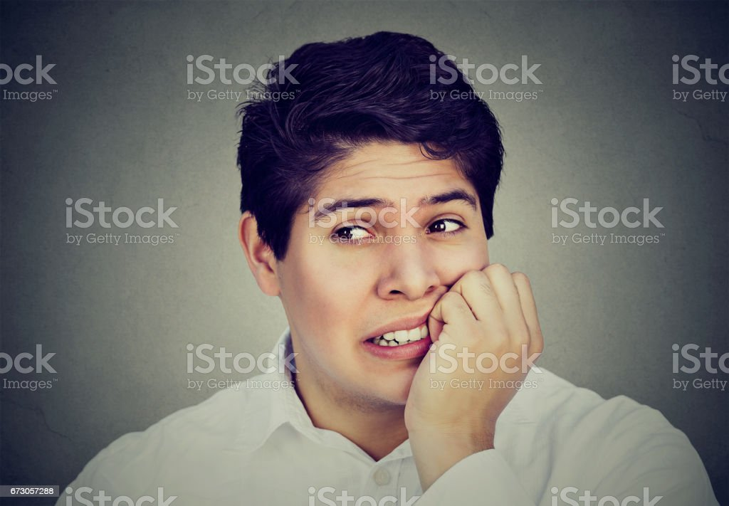 Portrait of an anxious man biting his fingernails freaking out stock photo