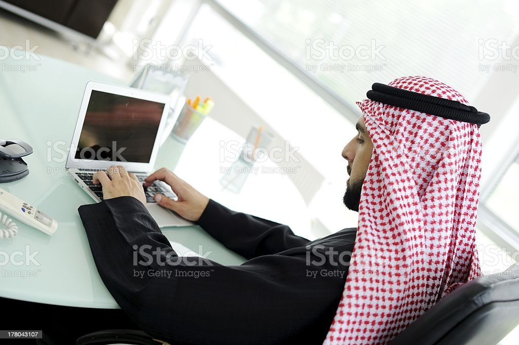 Portrait of an Arab at a desk using a small netbook stock photo