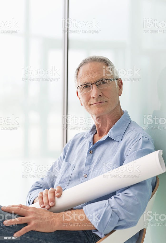 Portrait of an architect sitting with blueprint in hand royalty-free stock photo