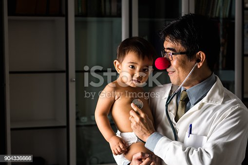 istock Portrait of an asian doctor with a clown red nose and a cute baby 904336666
