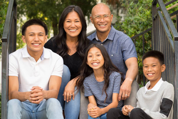 Portrait of an Asian family laughing and talking outside. Happy family sitting outside talking and spending time together. filipino ethnicity stock pictures, royalty-free photos & images
