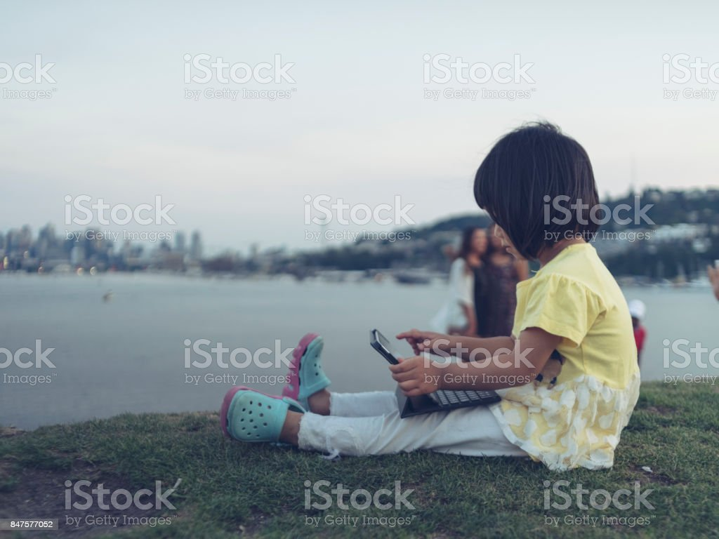 portrait of an asian little girl playing with tablet at lawn stock photo