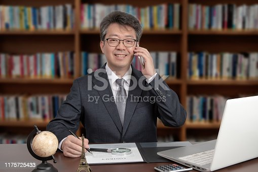 960195072 istock photo A portrait of an Asian middle-aged male businessman sitting at a desk, smiling and talking on the phone 1175725433