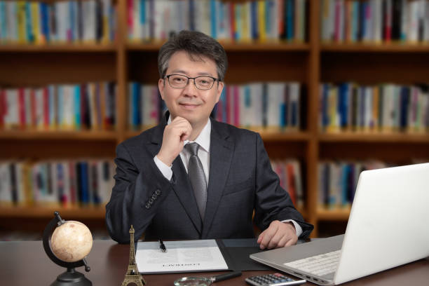 A portrait of an Asian middle-aged male businessman sitting at a desk. stock photo