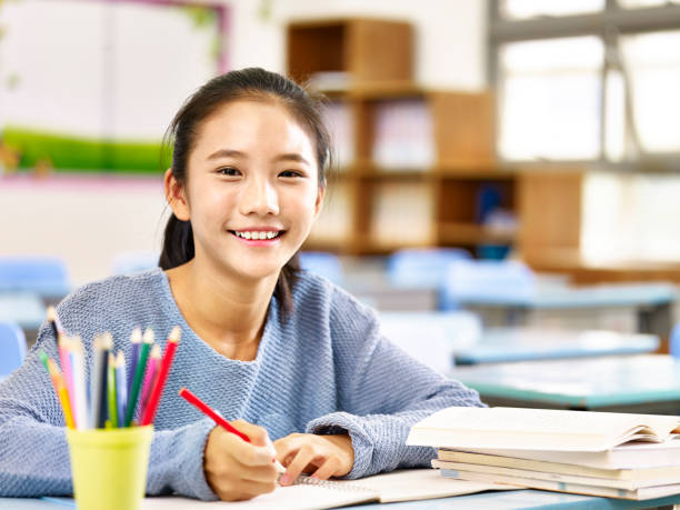 portrait of an asian schoolgirl happy asian elementary school student studying in classroom looking at camera smiling, japanese school girl stock pictures, royalty-free photos & images