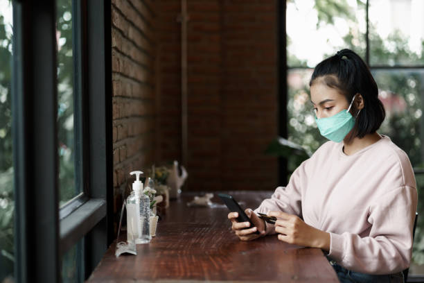 Portrait of an Asian teenager woman with face mask to prevent COVID-19 while chill out and make payment through credit card and phone in the cafe. Stock photo. stock photo