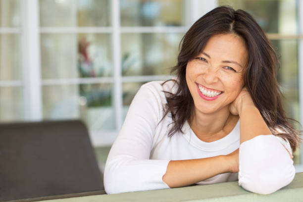 Portrait of an Asian woman smiling. Portrait of an Asian woman laughing and smiling. asian middle aged woman stock pictures, royalty-free photos & images