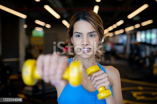 Portrait of an athletic woman working out at the gym using free-weights – active lifestyle concepts