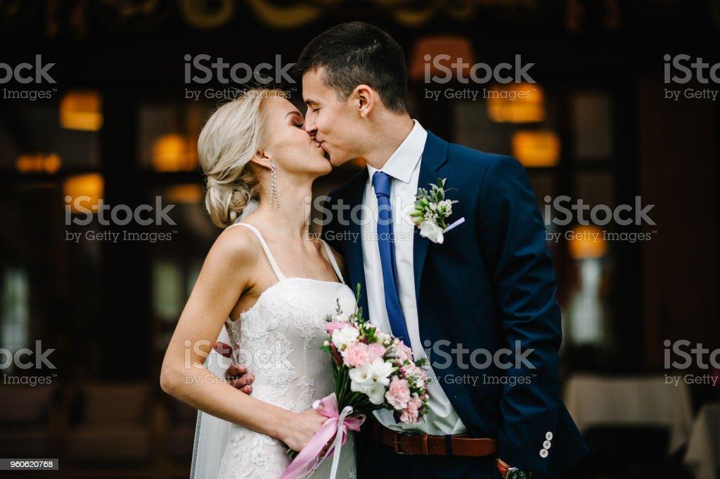 Porträt eines attraktiven Braut, die den Bräutigam und die Holding Bouquet von Rosa und lila Blumen und grünen mit Band bei der Hochzeitszeremonie umarmt. – Foto