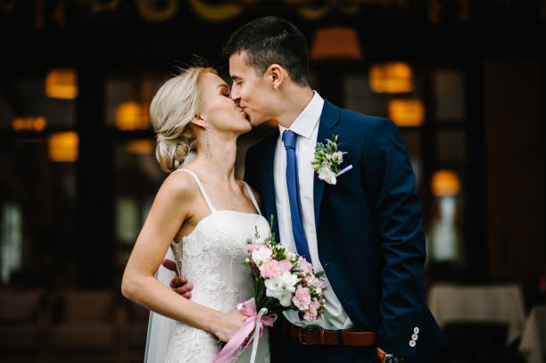 Portrait of an attractive bride who embraces the groom and holding bouquet of pink and purple flowers and greens with ribbon at the wedding ceremony. Portrait of an attractive bride who embraces the groom and holding bouquet of pink and purple flowers and greens with ribbon at the wedding ceremony. bridegroom stock pictures, royalty-free photos & images