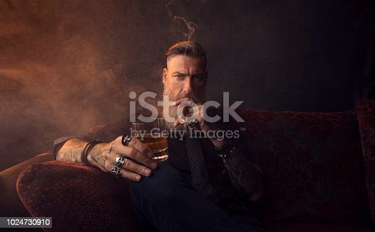 istock Portrait of an attractive business man with a cigar and a glass of whiskey in a dark room 1024730910