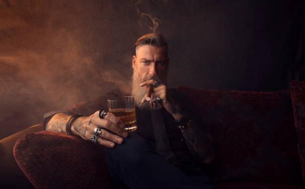 portret van een aantrekkelijke zakenman met een sigaar en een glas whisky in een donkere kamer - guy with cigar stockfoto's en -beelden