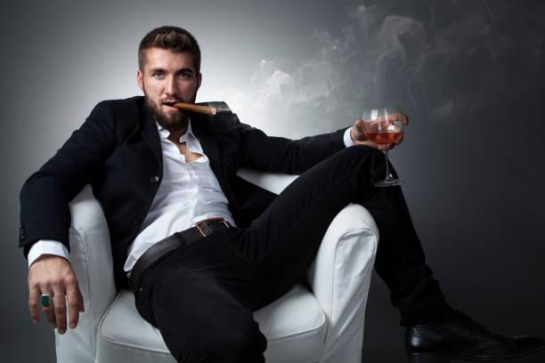 portret van een aantrekkelijke zakenman met een sigaar en een glas whiskey - guy with cigar stockfoto's en -beelden