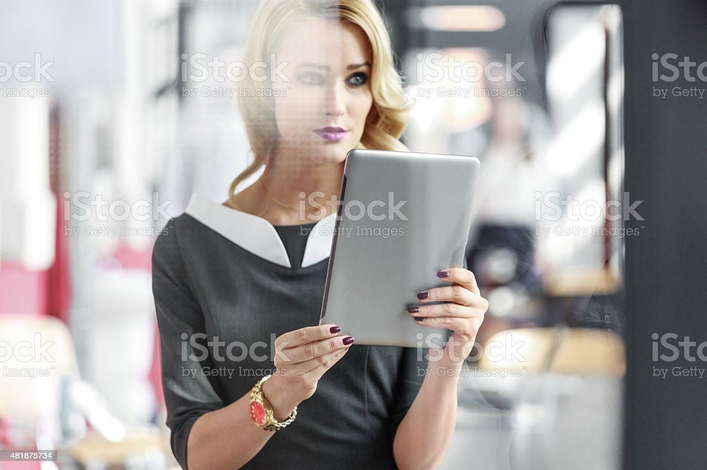 Portrait of an attractive businesswoman holding a digital tablet Portrait of beautiful blonde young businesswoman wearing grey dress sitting in an office and holding a digital tablet, looking away. Photo taken through glass. 2015 Stock Photo