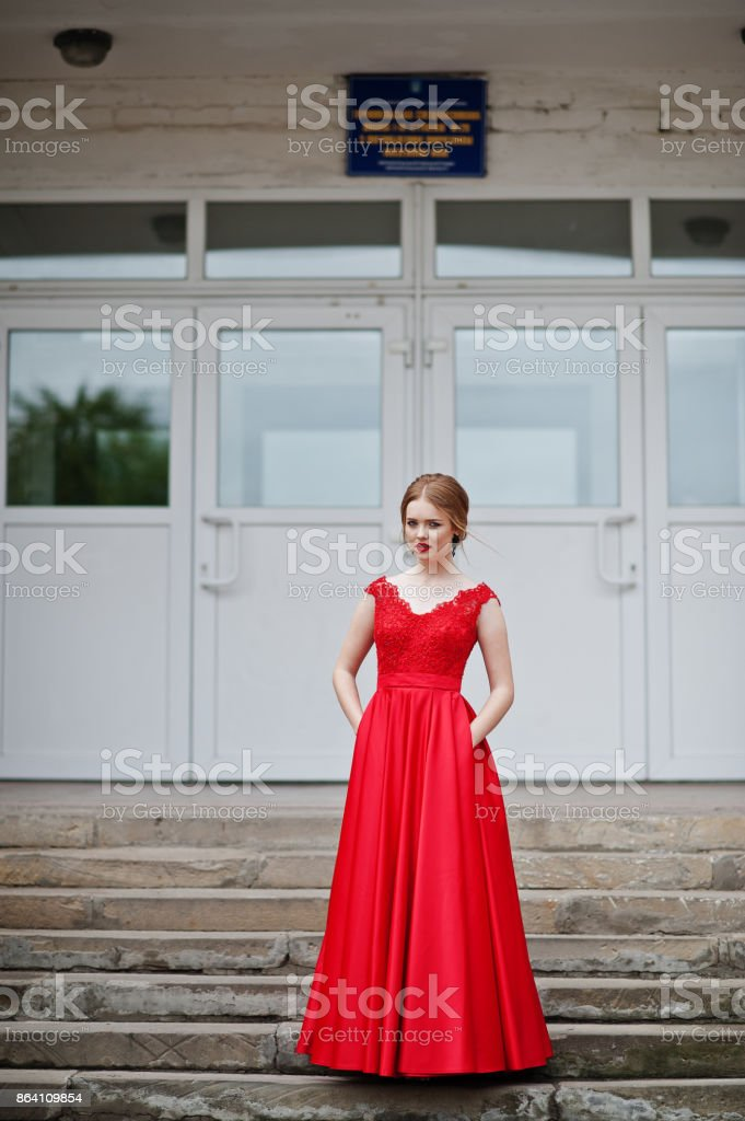 Portrait of an attractive girl standing and posing on the stairs in amazing gowns after high school graduation. royalty-free stock photo