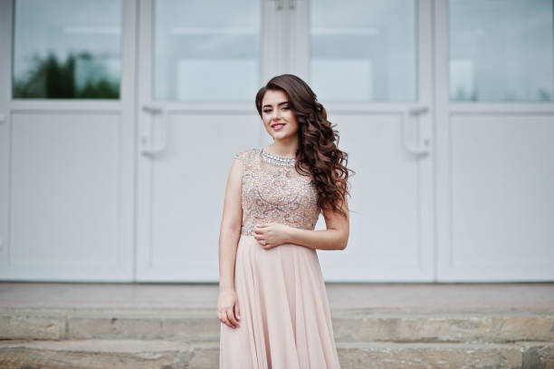 portrait of an attractive girl standing and posing on the stairs in amazing gowns after high school graduation. - prom stock photos and pictures