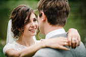 Portrait of an attractive groom looking bride on nature in the park. Wedding ceremony near lake. Happy and joyful moment.