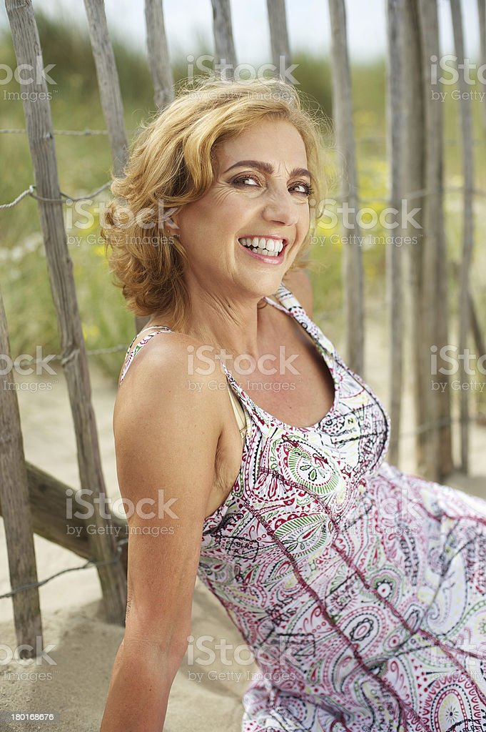 Portrait of an attractive mature woman smiling outdoors stock photo