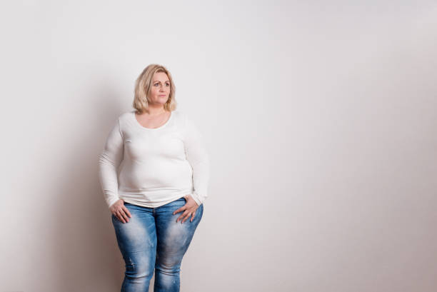 portrait of an attractive overweight woman in studio on a white background. - obesity foto e immagini stock
