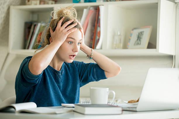 porträt einer attraktiven frau am tisch, die ihren kopf packt - frustration stock-fotos und bilder