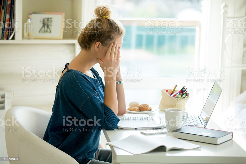 Portrait of an attractive woman at table hands at temples stock photo