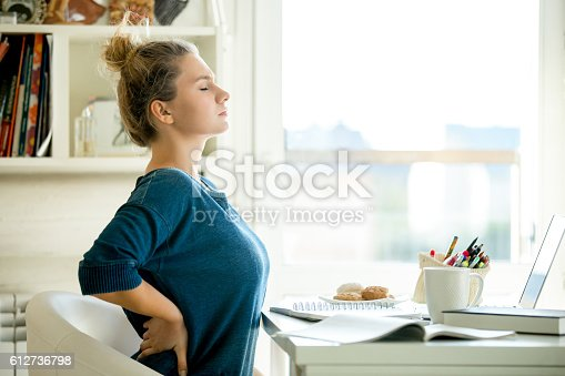 istock Portrait of an attractive woman at the table backache pose 612736798