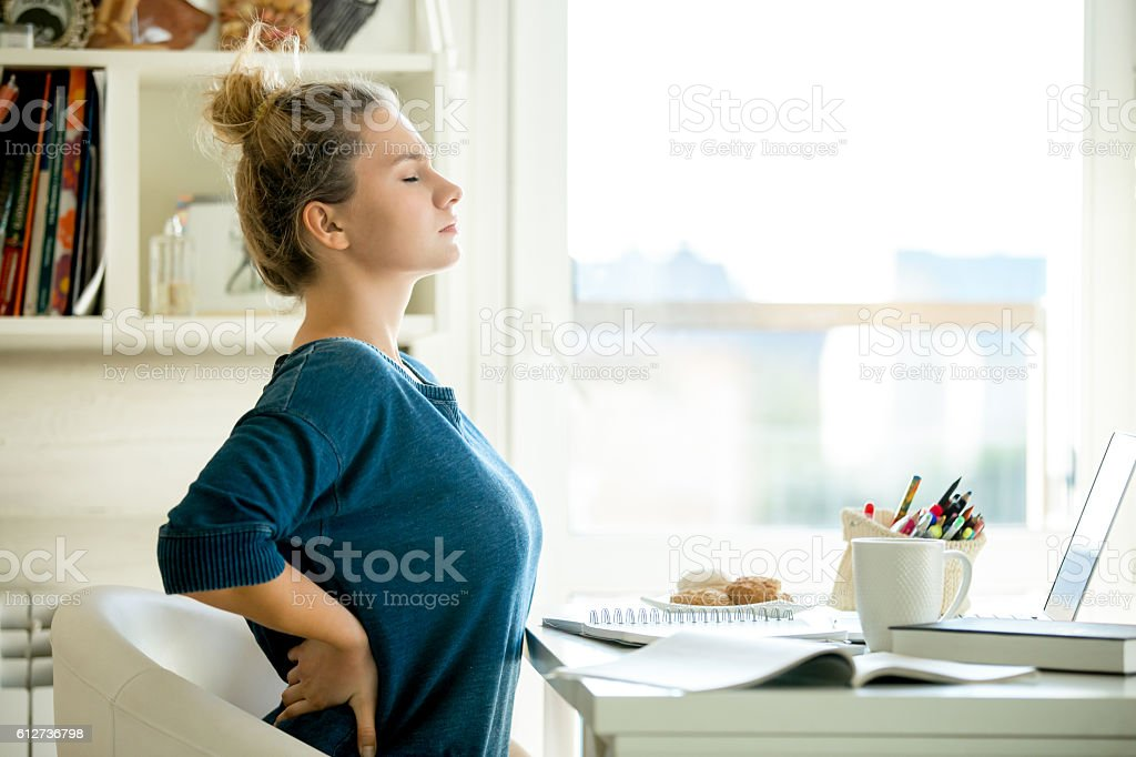 Portrait of an attractive woman at the table backache pose stock photo