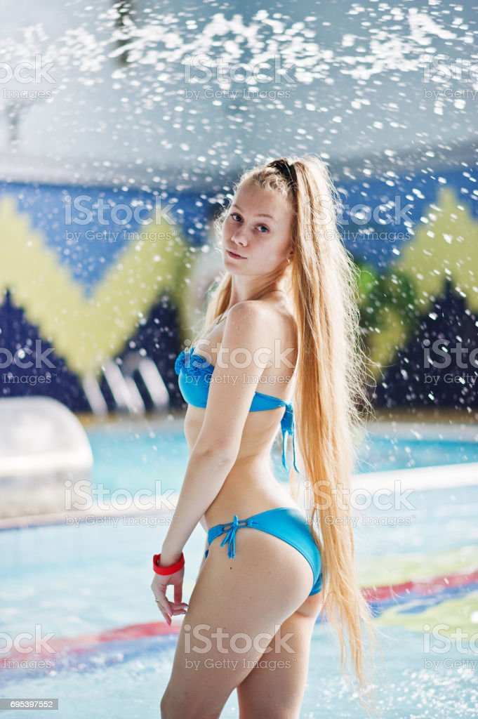 6b061ce2829c3 Portrait of an attractive young girl standing and posing in the pool  wearing blue bikini in the water park. - Stock image .