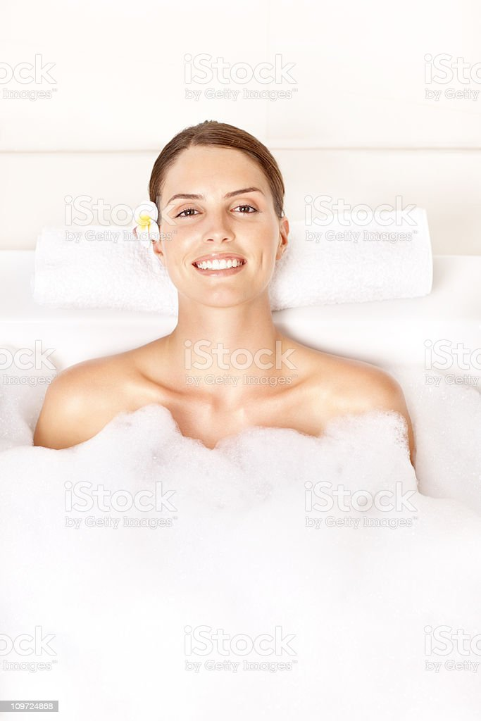 Portrait of an attractive young woman relaxing in bubble bath royalty-free stock photo