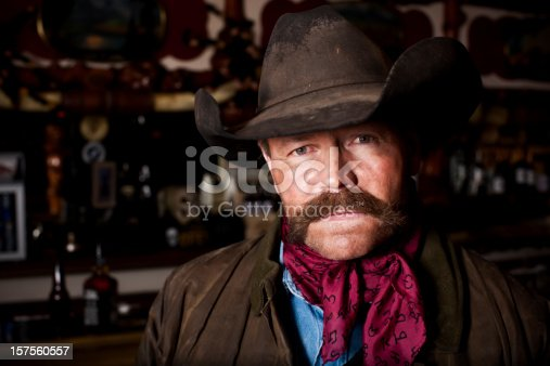 Head and shoulders portrait of a rough, weathered cowboy / rancher in a bar.