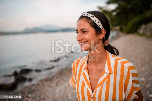 Portrait of an beautiful woman looking away. She is relaxing by the lake