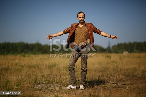 View at stylish dressed caucasian young man standing in a summer field, posing and looking at camera