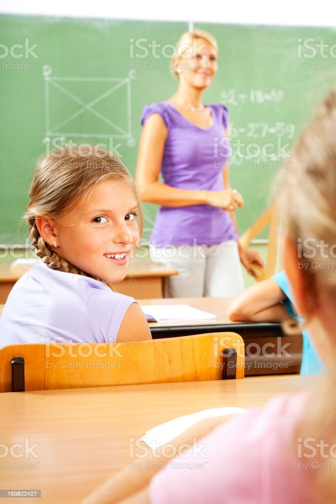 Portrait of an cute little school girl in the classroom royalty-free stock photo