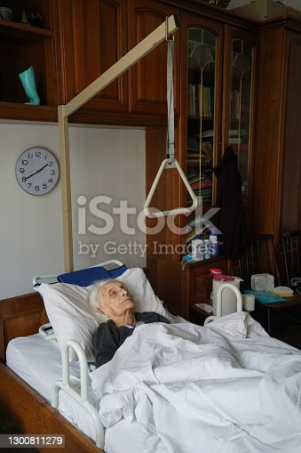 istock Portrait of an elderly immobile woman lying in bed at home. 1300811279