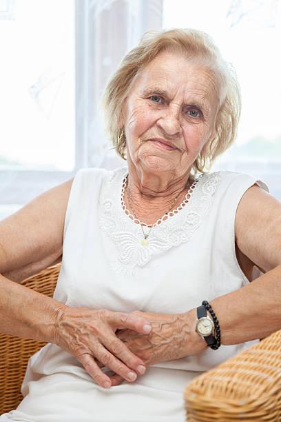 Portrait einer älteren Frau sitzt auf einem Stuhl – Foto