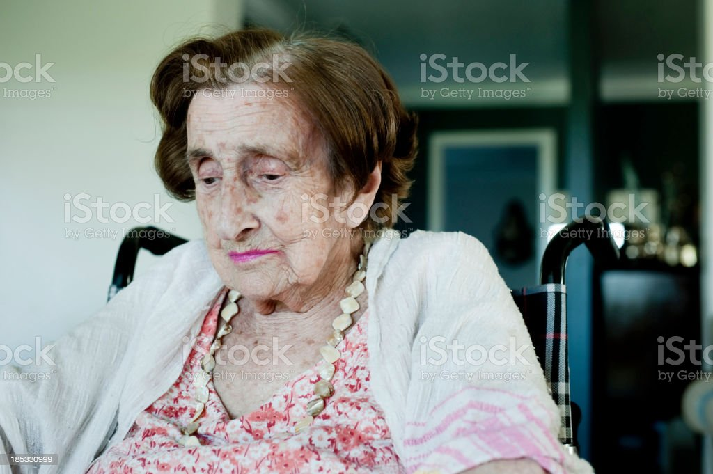 Portrait of an elderly woman in a wheelchair looking down  stock photo