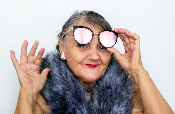 Portrait of an elderly woman with glasses. An old hipster lady with a fur collar and sunglasses. Older people, the concept of fashion. A fashionable hipster woman poses for the camera stock photo