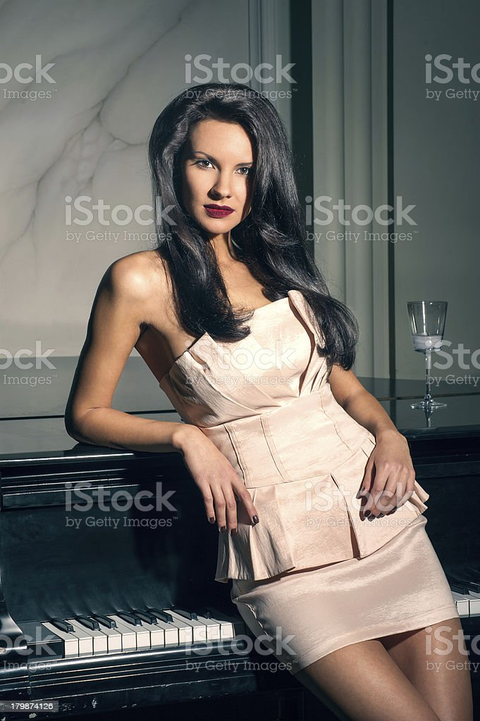 portrait of an elegant brunette on the piano royalty-free stock photo
