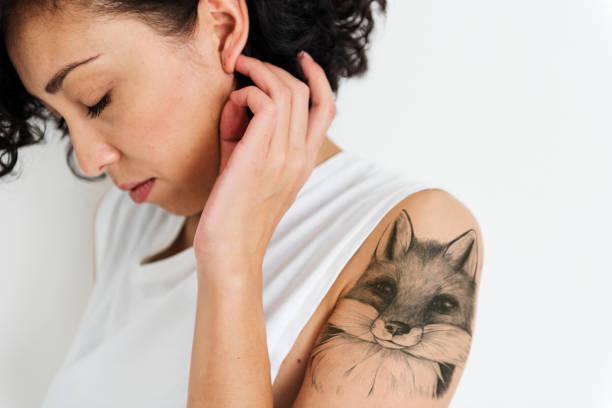 porträt einer emotionalen frau mit einer tätowierung - tattoos frauen arm stock-fotos und bilder