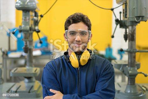 Portrait of an engineering student at the university wearing protective wear and smiling - education concepts