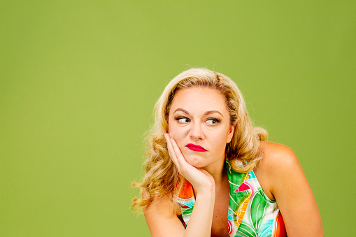 istock Portrait of an envious woman in bad mood looking right, isolated on green studio background 1015805854