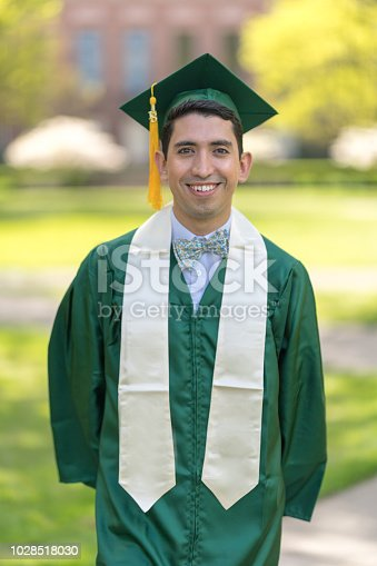 Portrait of a Columbian male graduate smiling on the university lawn in his cap and gown.