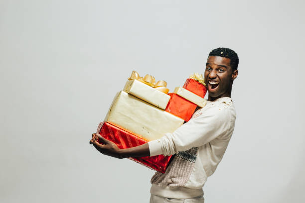 portrait of an excited young man carrying many gifts - carlos david stock pictures, royalty-free photos & images
