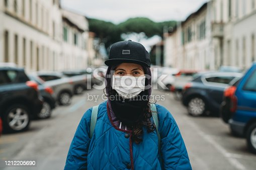 Portrait of an hip young girl in the city with a flu mask. She's protecting herself from viruses.