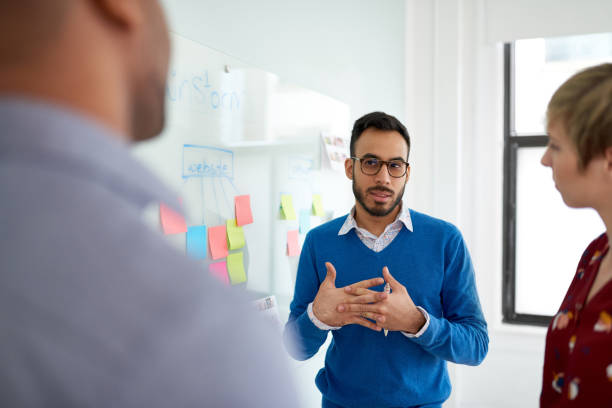 Portrait of an indian man in a diverse team of creative millennial coworkers in a startup brainstorming ideas stock photo