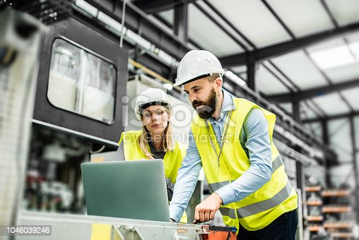 A portrait of a mature industrial man and woman engineer with laptop in a factory, working.