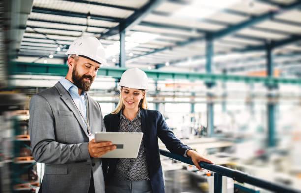 un retrato del ingeniero industrial del hombre y la mujer con la tablet en una fábrica, trabajando. - ingeniero fotografías e imágenes de stock